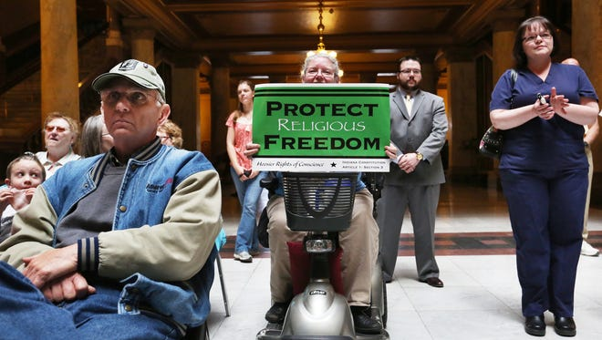 Cindy Holmes (center), Mechanicsburg, was one of more than 150 people who showed up at the Indiana Pastors Alliance rally to express their opposition to the changes made to the Religious Freedom Restoration Act.