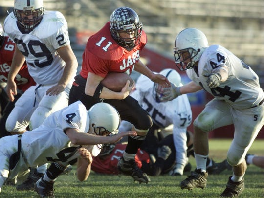 Jackson Memorial's Nick Castellano is chased by Shawnee's Dan MacDonald and Keith Smith during a 2000 football game.