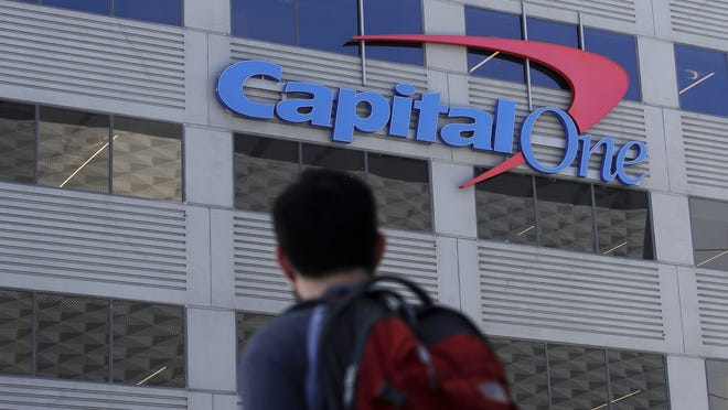 A man walks across the street from a Capital One location in San Francisco.