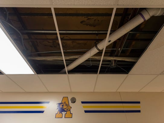 Patches of ceiling tiles have been removed at locations