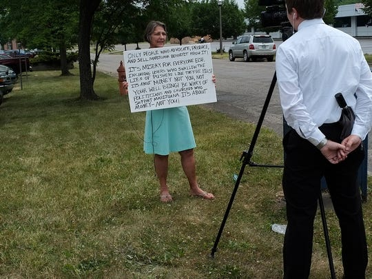 One of two women protest in front of a TV camera about the opening of the First Cannabis Church of Logic and Reason Sunday, June 26, 2016.