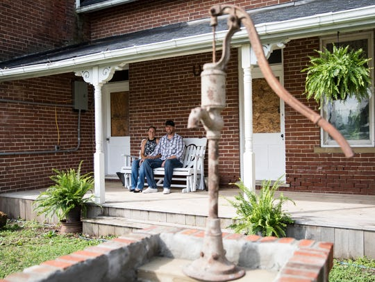 Bethany and Todd Snowden sit on the porch of a historical