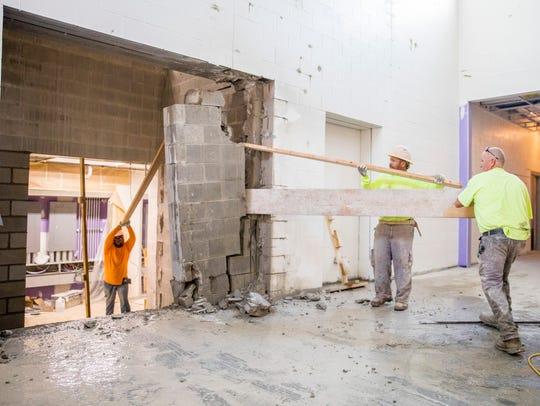 Construction crew members work on demolishing a wall
