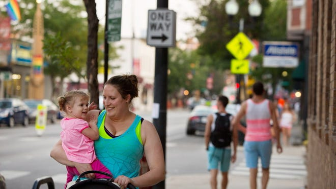 Nicole Landech walks along North Halsted Street with her 2-year-old daughter, Blair Silva, in Chicago's Boystown. Nationally, more straight people like Landech are living in historically gay enclaves.