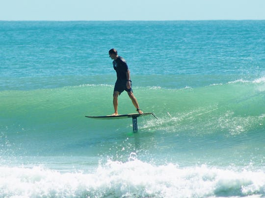 Cocoa Beach firefighter Laithem Kellum uses his hydrofoil surfboard to glide above the waves in Cocoa Beach.
