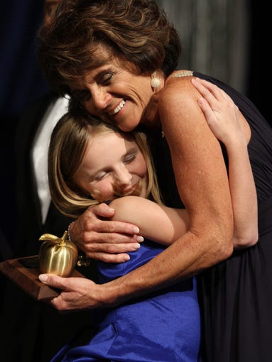 Sara Kohlhauff, of Pinewoods Elementary School, hugs student Abigail Beck after receiving her award during the 2014 Golden Apple Teacher Recognition Banquet at Harborside Event Center on Friday night.