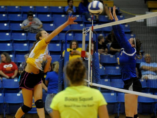 Mountain Home's Maly Tabor, left, hits as teammate Ashley Pyeatt, right, attempts to block during a practice at BomberFest on Friday night at The Hangar.