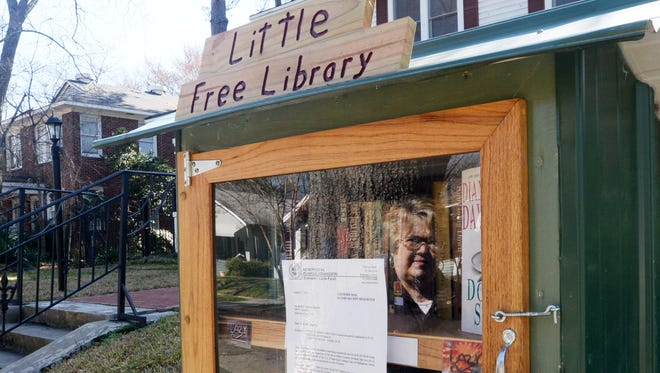 Teresa Edgerton is reflected in the Little Free Library that her husband, Ricky Edgerton, built for in front of their house on Wilkinson Street. The Metropolitan Planning Commission's zoning division forced the Edgertons to cease operating their Little Free Library after receiving anonymous complaint. According to the division, the library is considered a commercial enterprise.