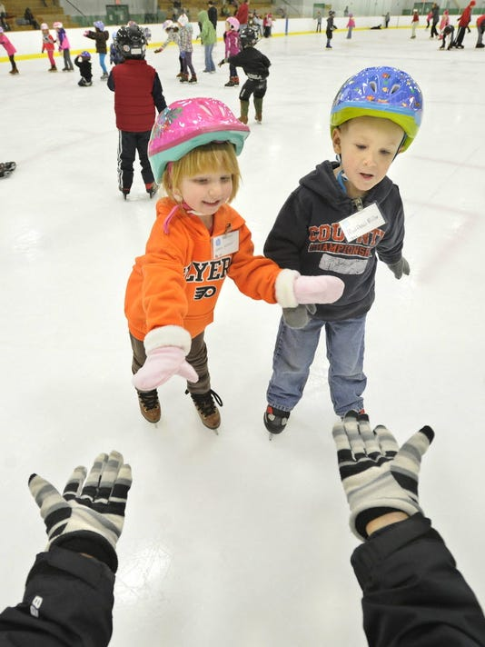 Then-4-year-old Emma Witter, left, and then-3-year-old Matthew Miller try to skate over to instructor Adriene Petrillo during the duo's lessons in November 2012 at the York Ice Arena. To keep up with your fitness goals, set aside time for some fun physical activity with family and friends. (Daily Record/Sunday News -- Jason Plotkin)
