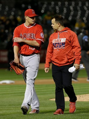Angels starter Garrett Richards, left, leaves the field with a trainer after being relieved during the fifth inning of the Angels' game against the Athletics in Oakland, Calif.