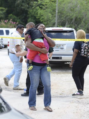 Parents pick up their children Friday, Aug. 18, 2017, from In His Arms Christian Academy in Pensacola. Police are investigating the death of a 3-year-old at the day care.