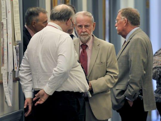 Senators and their staff talk in a Legislative Hall