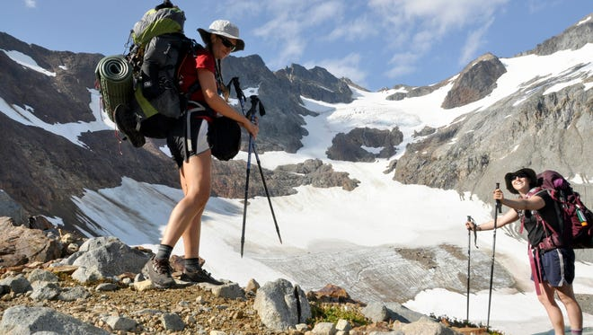 Holly Weiler, left, and Samantha Journot of the Spokane Mountaineers hike past Lyman Glacier as they head toward Spider Gap to complete a loop backpacking trek in Washington state's Glacier Peak Wilderness in August 2013. The U.S. Forest Service is proposing rules that restrict filming and photography by media organizations and others in more than 100 million acres of the nation's wilderness, Wednesday, Sept. 24, 2014.