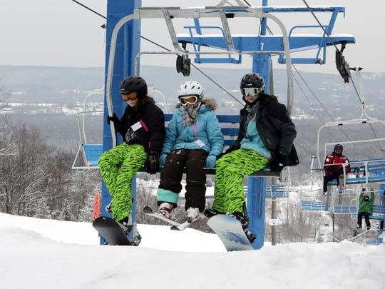 From left, Carly Corbett, 13, Caroline Cherubini, 10, and Bethany Cherubini, 13, all of Brewster, spend a day off from school skiing and snowboarding as they ride the chair-lift to the top Thunder Ridge on Jan. 25, 2011.