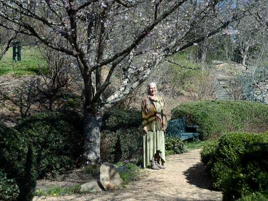 Shelli Stanback stands in the meditation garden of the OM Sanctuary campus in Asheville on Wednesday, March 23, 2016.  The non-profit has placed much of their 54 acre property on a conservation easement protecting an urban forest near the French Broad River.