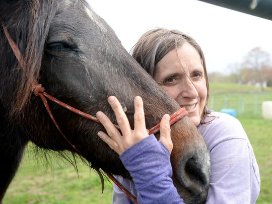 Volunteer Robin Hughes gives horse Biscuit a hug as she grooms him at Sweetwater Youth Ranch on Thursday, April 7, 2016.