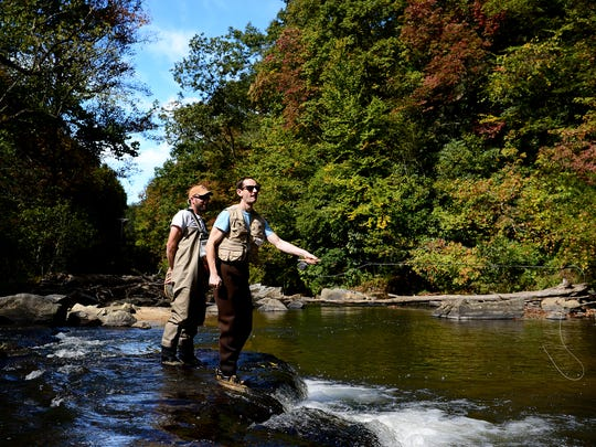 Matt Christian, an education specialist with the North Carolina Wildlife Resources Commission, watches as Giles Simpson, of Wilmington, casts into the river during an introduction to fly fishing class on the East Fork of the French Broad River near Rosman on Tuesday, Oct. 11, 2016.
