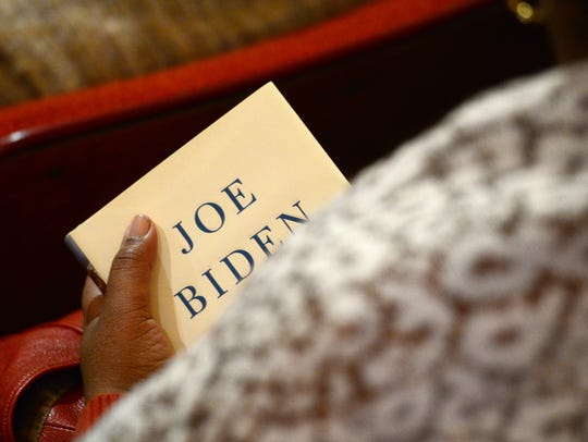 """A woman holds """"Promise me, Dad"""" by Joe Biden in her"""