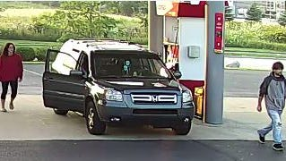 Both suspects and their vehicle at a gas pump.