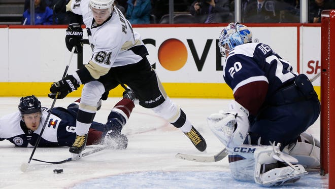 Pittsburgh Penguins left wing Sergei Plotnikov, center, skates past Colorado Avalanche defenseman Erik Johnson, left, to direct a shot on goalie Reto Berra, in the third period Wednesday in Denver. The Penguins won 4-2.