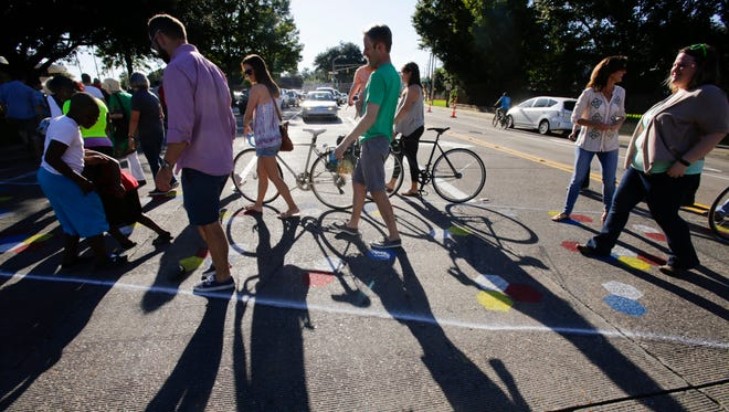 Bikers and pedestrians cross West Congress during the Complete Street Congress Block Party!, to celebrate the completion of new painting of traffic and bike lanes and crosswalks near the main library in Lafayette Oct. 8, 2016.