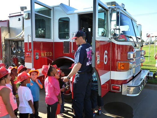 Wichita Falls firefighter Stuart Sutherland teaches Lamar Elementary kindergarten students about a fire engine and basic fire safety rules during a field trip Friday at First National Bank.