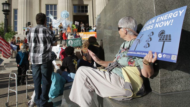 Leslie Lawson found a spot in front of Louisville Metro Hall to listen to speakers during a rally of the Louisville People's Climate March.  The groups started at the Federal Building at Sixth and Broadway and marched to Louisville Metro Hall. Oct. 14, 2015