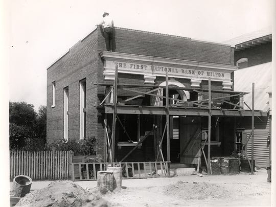 A construction worker working on the 100 year old building now home to the Bacchus Wine Bar of Milton. Back then, it was used as the town's bank.