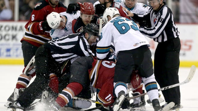 Tucson Roadrunners center Laurent Dauphin (15) gets swarmed under a dog pile of players against the San Jose Barracuda in Tucson on March 25.