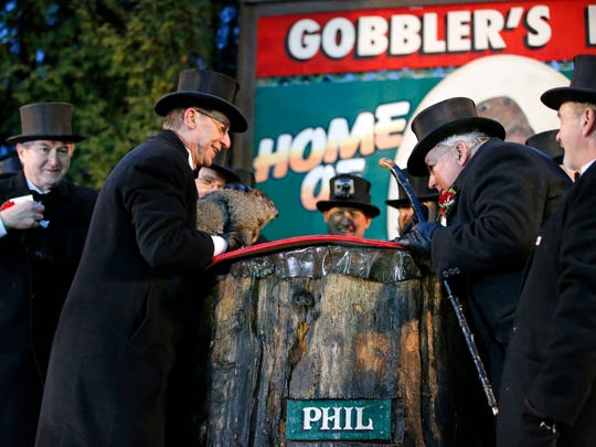 Groundhog Club handler Ron Ploucha, left, holds Punxsutawney