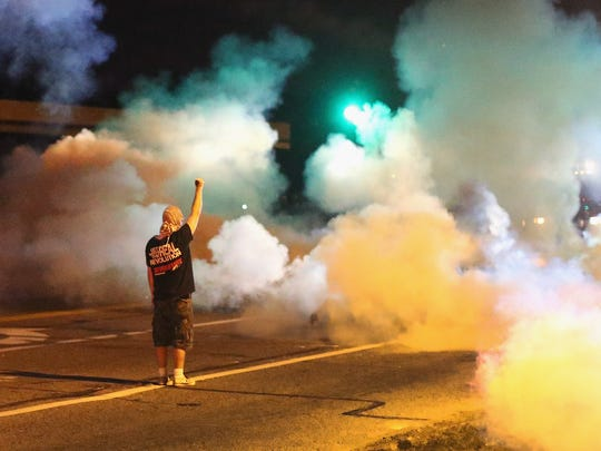 A demonstrator, protesting the shooting death of teenager Michael Brown, stands his ground as police fire tear gas on Wednesday in Ferguson, Mo.