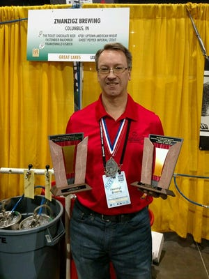 ZwanzigZ brewmaster Mike Rybinski holds the two silver medals and Small Brewpub and Small Bewbpub of the Year awards at the Great American Beer Festival.