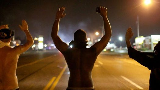 Demonstrators raise their arms in August as they protest the shooting death of Michael Brown.