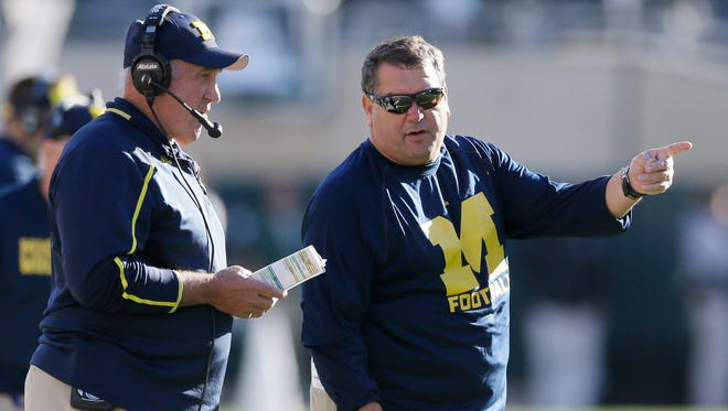 Michigan football coach Brady Hoke, right, works against Michigan State in East Lansing on Saturday, Oct. 25, 2014.