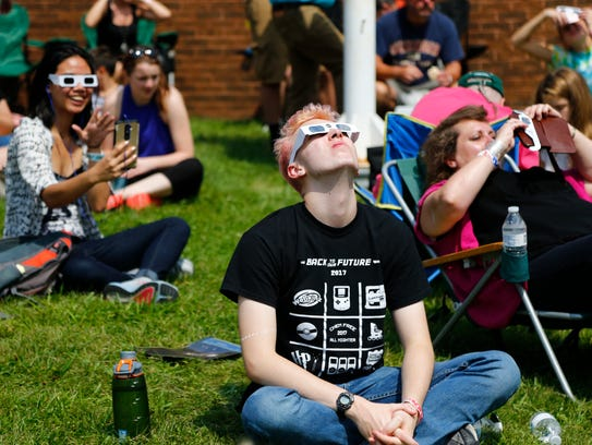 Noah Leveille of Vestal watches the solar eclipse at