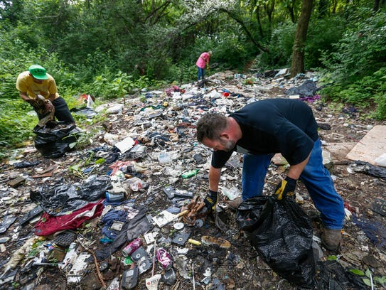 Barry Agee, right, and other volunteers clean up a
