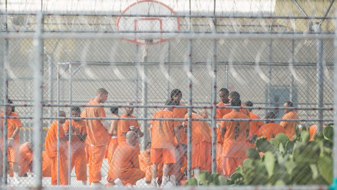 Prison inmates are seen on the yard through the fence at Arizona State Prison-Kingman.