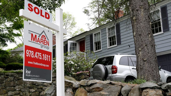 """In this May 24 file photo, a """"Sold"""" sign is placed front of a house in Andover, Mass. Mortgage rates are rising in the aftermath of Donald Trump's election victory."""