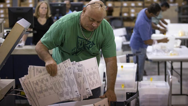 An election worker collects absentee ballots during a mechanical recount at the tabulation center in Riviera Beach on Sunday.