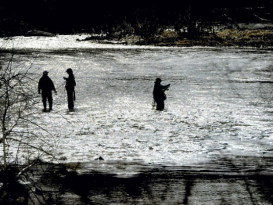 Fishermen make their way into the center of Muddy Creek in Fawn Township during the first day of fishing season on Saturday.