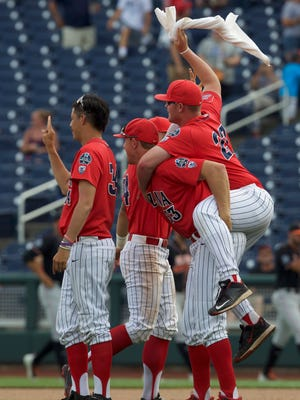 Arizona Wildcats pitcher Robby Medel (34) and pitcher Austin Schnabel (33) and pitcher JC Cloney (27) celebrate after defeating the Oklahoma State Cowboys in the College World Series at TD Ameritrade Park. Arizona won 5-1.
