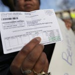 In Flint on Jan. 25, 2016, a frustrated and angry Claudia Perkins-Milton holds her water bill during a rally where about 100 people demanded not to have to pay for water that is not fit for human consumption.