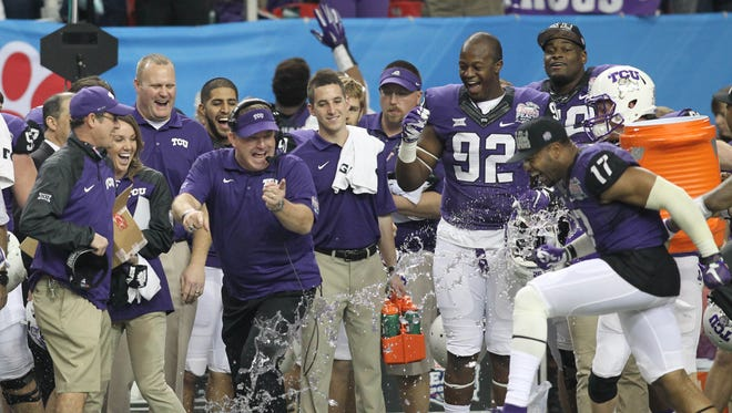 TCU Horned Frogs head coach Gary Patterson avoids the gatorade dunk following their 42-3 victory over the Mississippi Rebels in the 2014 Peach Bowl at the Georgia Dome.