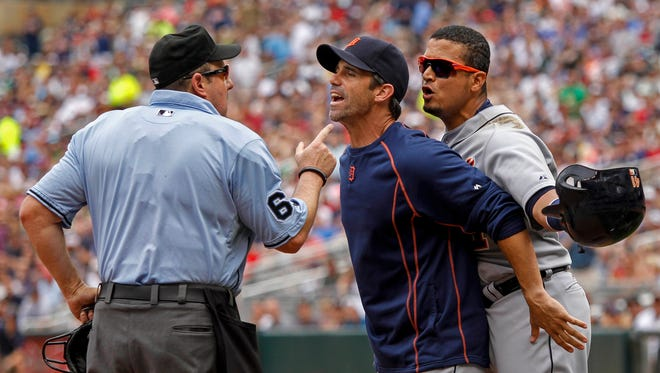 Jul 11, 2015; Detroit Tigers designated hitter Victor Martinez (41) reacts to his ejection from umpire Marty Foster as manager Brad Ausmus holds Martinez back in the fifth inning of the game with the Minnesota Twins at Target Field.