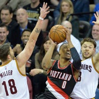 Jan 28, 2015; Cleveland, OH, USA; Portland Trail Blazers guard Damian Lillard (0) drives against Cleveland Cavaliers guard Matthew Dellavedova (8) and guard Mike Miller (18) in the second quarter at Quicken Loans Arena. Mandatory Credit: David Richard-USA TODAY Sports