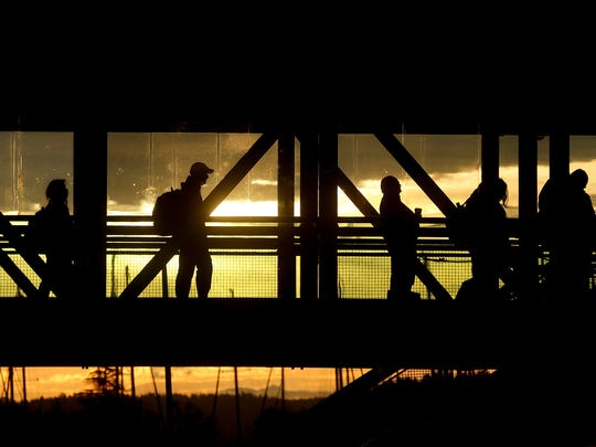 Commuters are silhouetted against the rising sun as