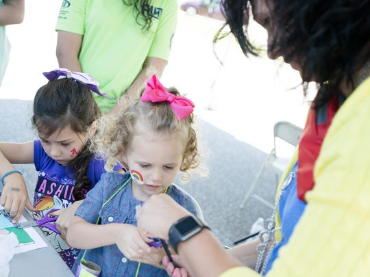 From right, Lexcie Potter helps her daughter's Ari and Savannah with a art project during the FLIMP Festival at Montgomery Museum of Fine Arts on Saturday, May 6, 2017, in Montgomery, Ala.