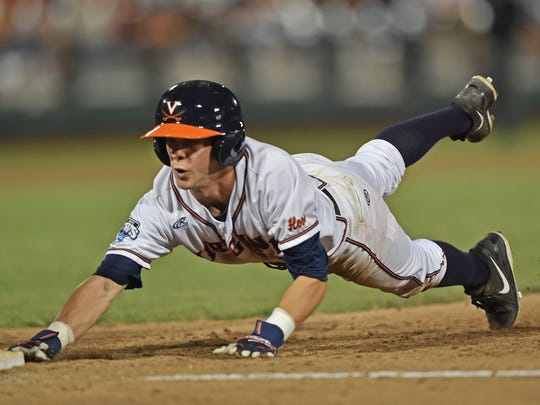 Base runner Ernie Clement #4 of the Virginia Cavaliers dives back to first base safely against the Vanderbilt Commodores in the College World Series Championship Series on June 23, 2015.