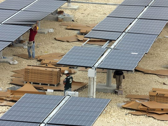 Workers install solar panels in 2009 at the FGCU solar farm, in front of the university.