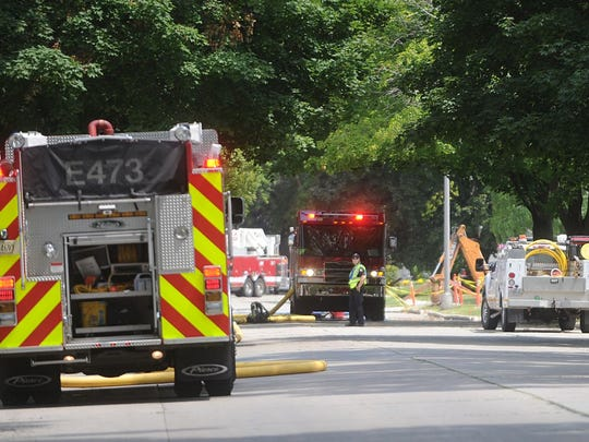 City of Fond du Lac firefighters stand by at 9th and Lloyd streets Thursday as officials from Alliant Energy work to shut off gas to a six-inch gas main that was punctured by a backhoe.
